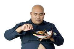 Fat man eating, portrait of overweight person feels hungry and e. Ating chips,cake,green tea frappe seated on armchai, isolated on white background with clipping stock photo