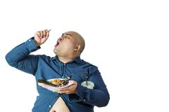 Fat man eating, portrait of overweight person feels hungry and e. Ating chips,cake,green tea frappe seated on armchai, isolated on white background with clipping stock images
