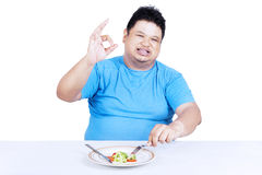 Fat man eating salad 1 Stock Images
