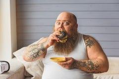 Fat man eating unhealthy burger at home Royalty Free Stock Photography