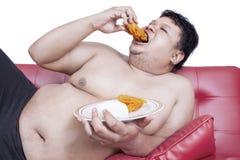 Fat man eats fast food 2 Stock Photos