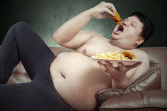 Fat man eats junk food Royalty Free Stock Image