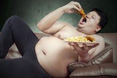 Fat man eats junk food. Fat man eats fast food while sitting on sofa at home Royalty Free Stock Image