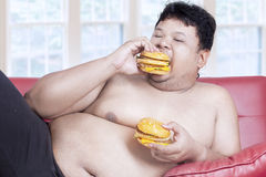 Fat man eats two hamburgers 1 Royalty Free Stock Images