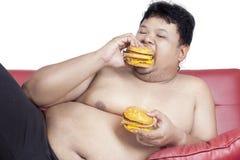 Fat man eats two hamburgers 2 Royalty Free Stock Photo