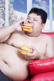 Fat man eats two hamburgers. Portrait of fat man eating two hamburgers while sitting on red couch with winter background on the window Royalty Free Stock Photography