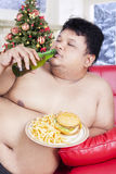 Fat man enjoy fast food in christmas day Stock Photos