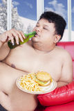 Fat man enjoy junk food in winter season. Portrait of fat man sitting on the sofa while enjoying fresh beer and junk food in winter season Royalty Free Stock Photo