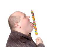 Fat man enjoying a lollipop Stock Photos