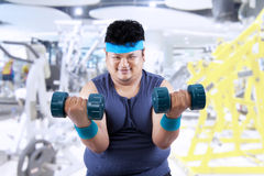 Fat man exercise in fitness center 2 Stock Photos