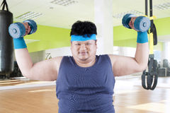 Fat man exercise in fitness center Royalty Free Stock Images