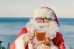 Fat man in glasses dressed as Santa drinking beer on the ocean. Funny, drunk and happy. Fat man dressed as Santa drinking beer on the ocean stock photo