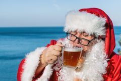 Fat man in glasses dressed as Santa drinking beer on the ocean. Funny, drunk and happy. Fat man dressed as Santa drinking beer on the ocean royalty free stock photography