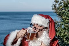 Fat man in glasses dressed as Santa drinking beer on the ocean. Funny, drunk and happy. Fat man dressed as Santa drinking beer on the ocean royalty free stock image