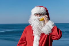 Fat man in glasses dressed as Santa holds banana on the ocean. Vacation and healthy lifestyle royalty free stock image
