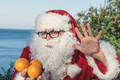 Fat man in glasses dressed as Santa holds tangerines on the ocean. Vacation and healthy lifestyle. Fat man in glasses dressed as Santa holds tangerines on the stock photos