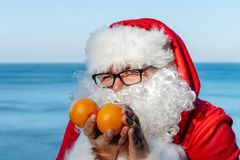 Fat man in glasses dressed as Santa holds tangerines on the ocean. Vacation and healthy lifestyle. Fat man in glasses dressed as Santa holds tangerines on the royalty free stock photo