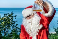 Fat man in glasses dressed as Santa pours beer from a mug to the ground. Santa against drunkenness. Fat man in glasses dressed as Santa pours beer from a mug to stock images
