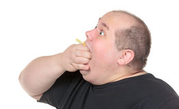 Fat Man Greedily Eating French Fries Royalty Free Stock Images