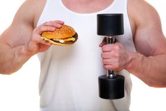 Fat man with a hamburger holds dumbbells  on white. The concept of choosing between harmful food and a healthy. Lifestyle. Portrait of overweight person who Royalty Free Stock Photos