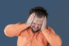 A fat man has high blood pressure and headache. Overweight and health problems stock images