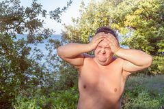A fat man has high blood pressure and headache. Overweight and health problems royalty free stock photography