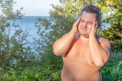 A fat man has high blood pressure and headache. Overweight and health problems stock image
