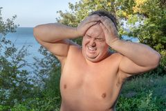 A fat man has high blood pressure and headache. Overweight and health problems royalty free stock photos