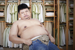 Fat man with his old jeans. Obese man trying to wear his old jeans Stock Photography