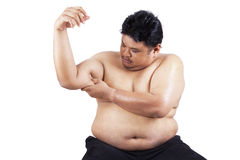 Fat man holding his flabby biceps 1. Fat man holding his flabby biceps, isolated on white background Royalty Free Stock Photography