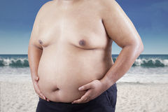 Fat man holding his stomach at beach 1 Stock Photo