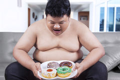 Fat man holding a plate of donuts Stock Photography