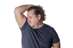 Fat man holds or pinches his nose shut because of a stinky smell or odor. Fat man holds or pinches his nose shut because of a stinky smell royalty free stock photography