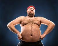 Fat man imitating muscular build Stock Images