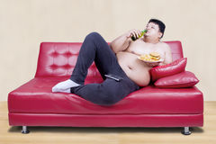 Fat man leaning on the couch Royalty Free Stock Image