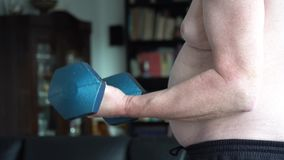 Fat man lifting dumbbell stock video
