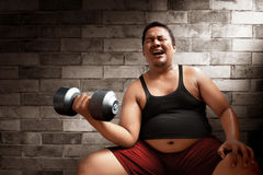 Fat man lifting weights. On brick wall background Stock Images