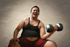 Fat man lifting weights. Fat man doing lifting weights Royalty Free Stock Image