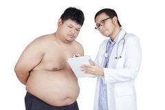 Fat man listening explaination of his doctor Royalty Free Stock Images