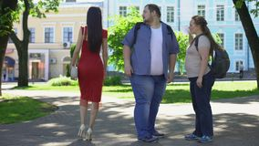 Fat man looking at beautiful lady in red passing by, obese girlfriend jealous. Stock footage stock video footage