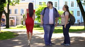 Fat man looking at beautiful lady in red passing by, obese girlfriend jealous. Stock photo stock images
