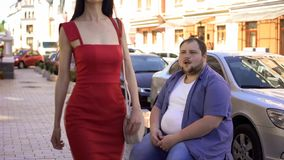 Fat man looking with delight at beautiful slim lady in red dress passing by. Fat men looking with delight at beautiful slim lady in red dress passing by, stock stock photos