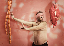 Fat man looking for sausages Stock Image