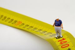 Fat man on a measurer - miniature Royalty Free Stock Photo