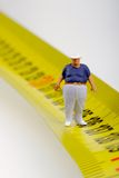 Fat man on a measurer - miniature Stock Images