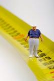 Fat man on a measurer - miniature Stock Images