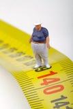 Fat man on a measurer - miniature Stock Photo