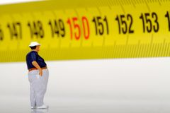 Fat man on a measurer - miniature Royalty Free Stock Images
