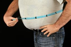 Fat man measuring his belly royalty free stock photo