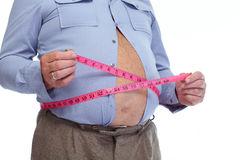Fat man measuring his big stomack. Royalty Free Stock Photography